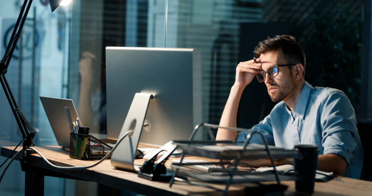 Frustrated businessman looking at his computer at the office
