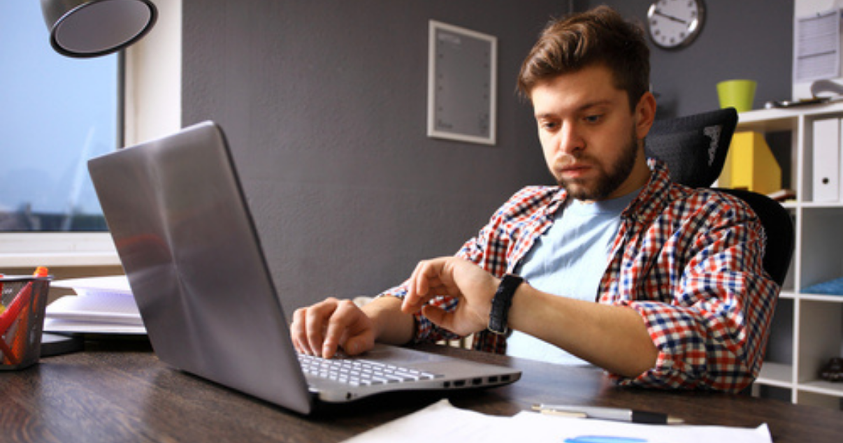 Man overwhelmed with paperwork looking at his watch