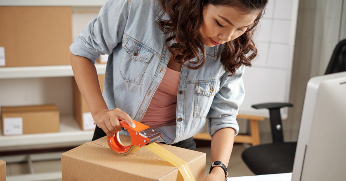 Online seller packing boxes for her ecommerce customers