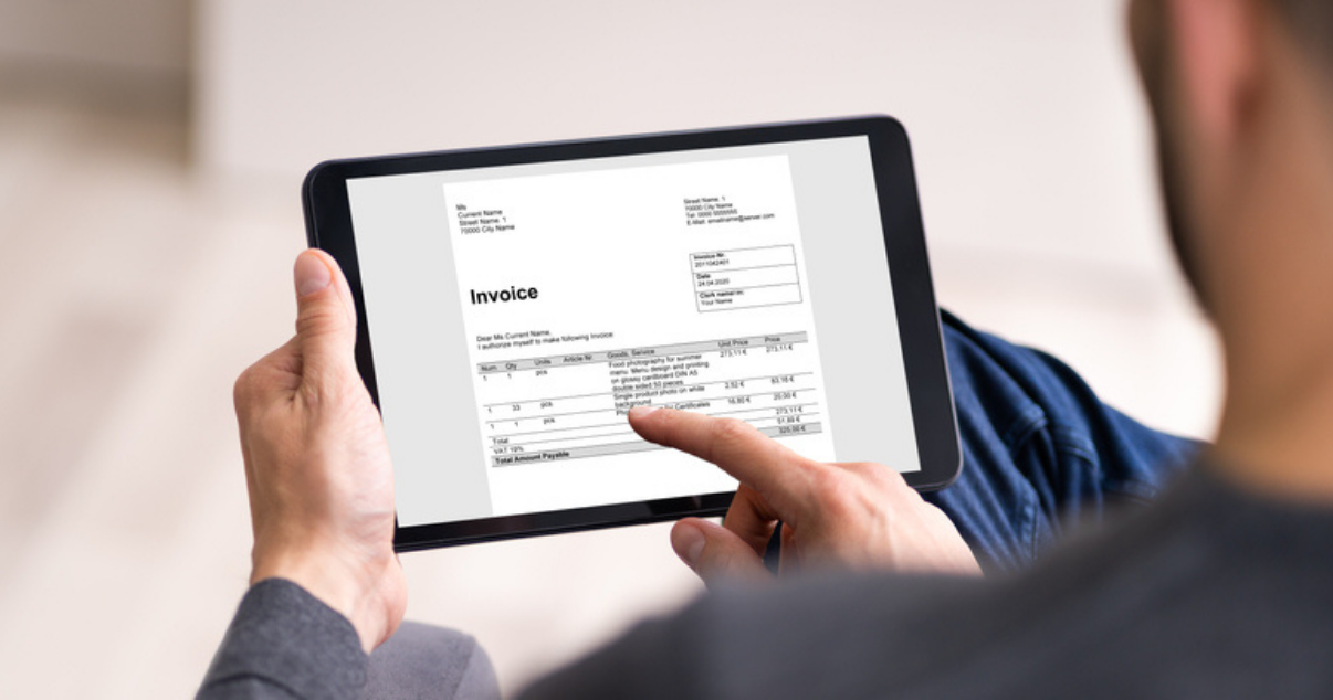 Man paying his invoices on his tablet